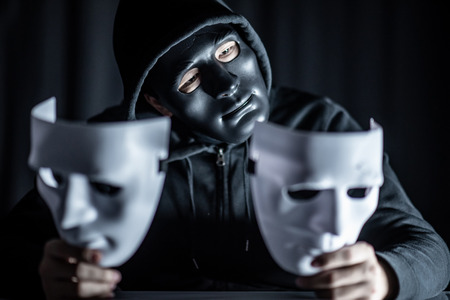Mystery hoody man wearing black mask holding two white masks in his hand. Anonymous social masking. Major depressive disorder or bipolar disorder. Halloween concept Stockfoto