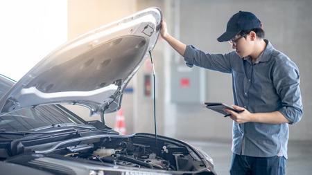 Asiatischer Automechaniker, der digitales Tablett hält, das den Automotor unter der Haube in der Autowerkstatt prüft. Maschinenbauingenieur in der Automobilindustrie. Wartung und Reparatur von Kraftfahrzeugen