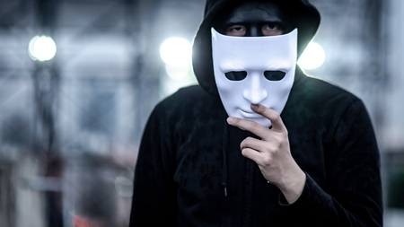 Mystery hoodie man with broken black mask holding white mask in his hand. Anonymous social masking or bipolar disorder concept. Stock Photo