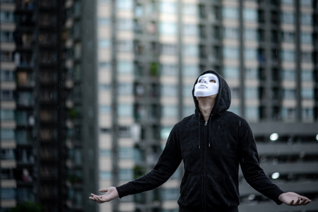 Mystery hoodie man in white mask standing in the rain looking up at the sky on rooftop of abandoned building. Bipolar disorder or Major depressive disorder. Depression concept