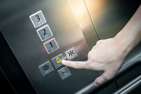 Male forefinger pressing on emergency stop and alarm button in elevator (lift). Mechanical engineering concept 스톡 콘텐츠