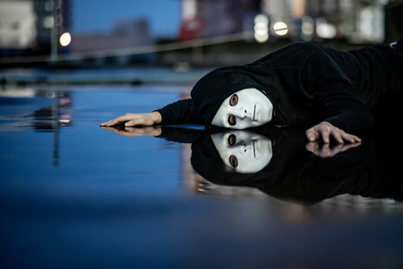 Reflection of mystery hoodie man in white mask feeling depressed and disappointed lying on wet floor after the rain. Sadness, depression and bipolar disorder concepts Stock Photo
