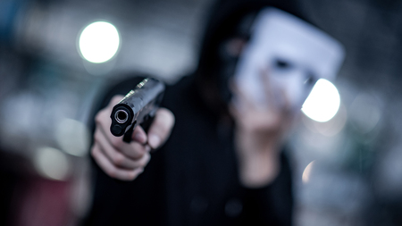 Mystery hoodie man in white mask pointing gun. Crime and violence concepts. Focus on gun 免版税图像