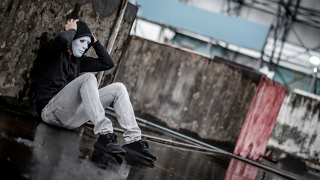 Mystery hoodie man in white mask feeling stressed sitting in the rain on rooftop of abandoned building. Bipolar disorder or Major depressive disorder. Depression concept 스톡 콘텐츠 - 117912651