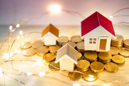 Concept d'investissement immobilier ou immobilier. Taux de prêt immobilier. Pile de pièces d'or, modèles de maison et lumières de Noël décoratives sur la table. Économiser de l'argent pour la future retraite.