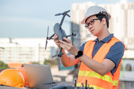 Asian engineer man working with drone, remote control and laptop computer at construction site. Using unmanned aerial vehicle (UAV) for land and building site survey in civil engineering project.
