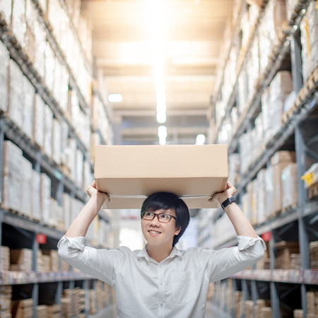 Asian delivery man carrying cardboard box overhead in product shelves aisle in warehouse. Inventory picking and packing. Shopping lifestyle in department store. Buying or purchasing factory goods