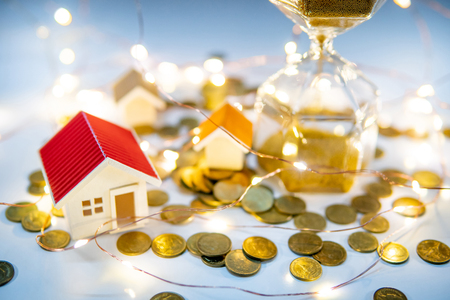 Real estate investment concept. Property marketing during festive holiday season. Hourglass with gold coins, house models and decorative lights on the table. Saving money for retirement. Stock Photo