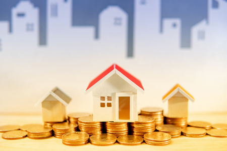 Real estate or property investment concept. Home mortgage loan rate. Gold coins stack and house models on the table with white city skyline background. Saving money for future retirement.