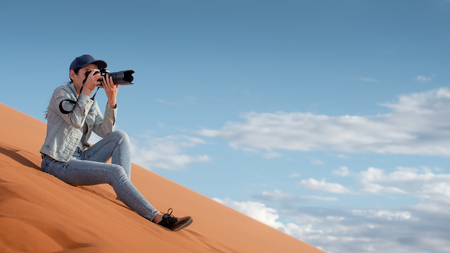 Young Asian woman traveler and photographer holding camera taking photo while sitting on sand dune in Namib desert of Namibia, Africa. Travel photography concept