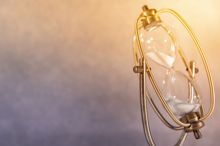 White sand running through the shape of vintage hourglass.Time passing and running out of time. Urgency countdown timer for business deadline concept