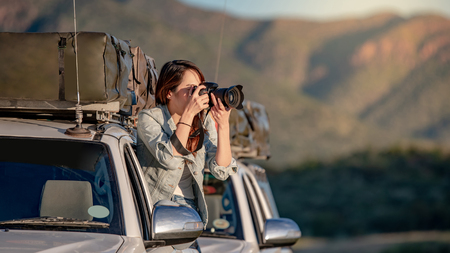 Young Asian woman traveler and photographer sitting on the car window taking photo on road trip in Namibia, Africa. Travel photography concept Stock fotó