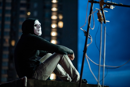 Mystery hoodie man in white mask sitting on rooftop of abandoned building during the twilight time. Bipolar disorder or Major depressive disorder. Depression concept