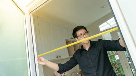 Young Asian worker man using tape measure on door frame in the kitchen. Home interior designer measuring elements on site. Housing design and construction concept Banque d'images - 118719015