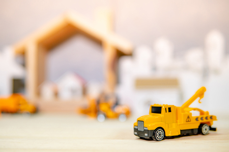 Miniature yellow crane truck model with blurred house frame and city background on wooden table. Architecture and construction industry concept Banco de Imagens