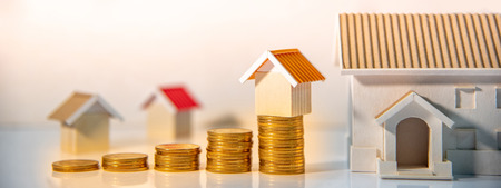 Real estate investment or Home mortgage loan rate. Property ladder concept. Coins stack and house models on the table. Money investing and business growth. Reklamní fotografie