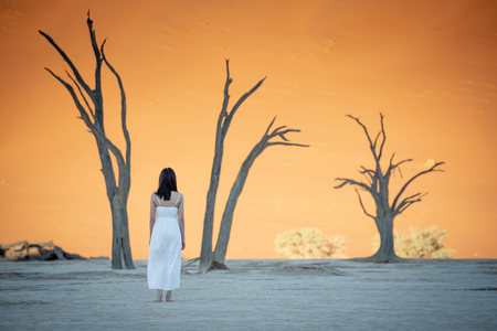 Young attractive Asian girl wearing white dress standing bear foot in deadvlei (Sossusvlei) during the sunrise, famous natural landmark in Namib desert of Namibia, Africa