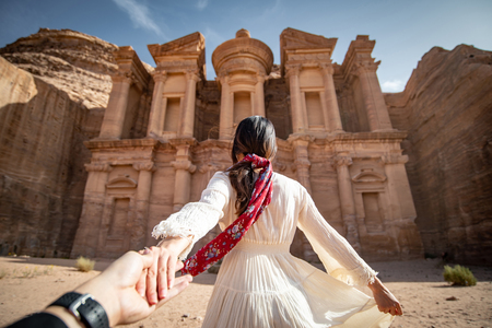 Asian woman tourist in white dress holding her couple hand at Ad Deir or El Deir, the monument carved out of rock in the ancient city of Petra, Jordan.