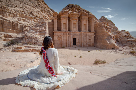 Asian woman tourist in white dress sitting and looking at Ad Deir or El Deir, the monument carved out of rock in the ancient city of Petra, Jordan.