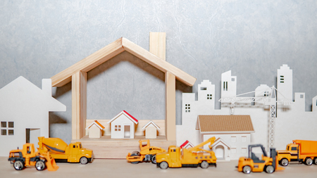 House models, paper crane and city background with miniature yellow trucks on wooden table. Architecture and construction industry for housing development business. Property or real estate concept