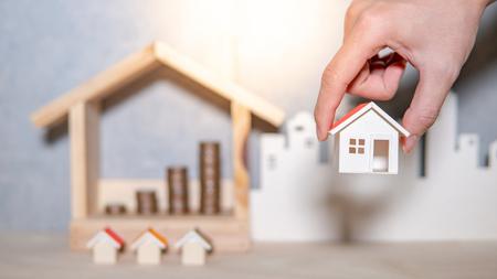 Inversión inmobiliaria o inmobiliaria en crecimiento empresarial. Tasa de préstamo hipotecario para vivienda. Ahorrar dinero para el concepto de jubilación. Mano masculina sosteniendo el modelo de la casa con pila de monedas borrosa en el marco de la casa sobre la mesa.