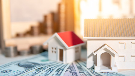 Property or real estate investment concept. Home mortgage loan rate. Saving money for future retirement. Miniature house model with stacked coins and dollar currency banknotes on wooden table.