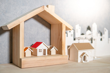 Property or real estate investment concept. Home mortgage loan rate. Saving money for future retirement. Miniature house model with paper city background and construction crane on wooden table. Archivio Fotografico