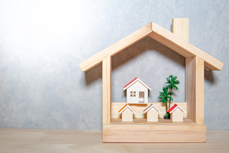 Real estate or property investment. Residential building development. Group of house models and tree in wooden house frame with city background. Home design and construction concept