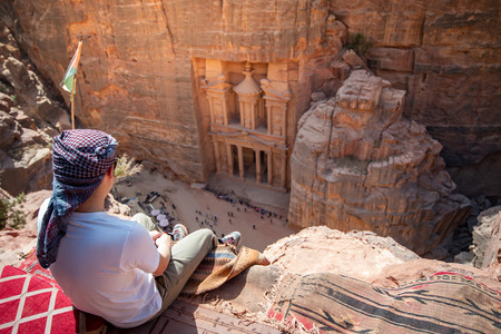 Asian man traveler sitting on carpet viewpoint in Petra ancient city looking at the Treasury or Al-khazneh, famous travel destination of Jordan and one of seven wonders. Banco de Imagens