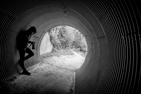 Mystery hoody man holding DSLR camera leaning in the tunnel. Travel photography concept
