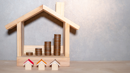 Property or real estate investment concept. Home mortgage loan rate. Saving money for future retirement. Miniature house model with coins stacked in wood house frame on wooden table. Stock Photo