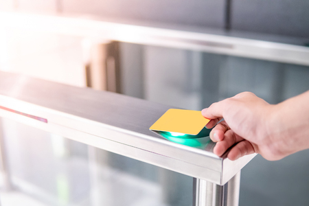 Male hand using smart card to open automatic gate machine in office building