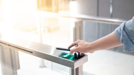 Male hand using smartphone to open automatic gate machine in office building Banque d'images - 122381856