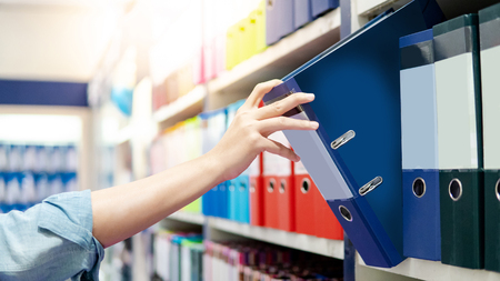 Male hand choosing new blue ring binder file folder from colorful shelf display in stationery shop. Buying office supplies concept
