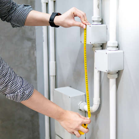 Male hand electrician using tape measure for measuring dimension of electrical conduit and electrical box on the wall. Electrical fitting installation and building construction concepts Zdjęcie Seryjne - 150981219