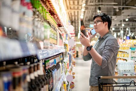 Asian man using smartphone while shopping beer in supermarket. Male shopper with shopping cart choosing beer bottle in grocery store.