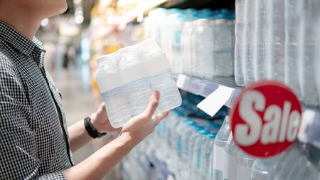 Male shopper picking pack of mineral water bottle from product shelf in supermarket. Customer shopping drinking water in grocery store. Healthy lifestyle