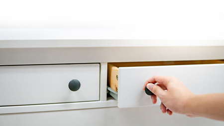 Male hand pulling and opening drawer on white wooden cabinet. Home furniture and decoration shopping concept Archivio Fotografico