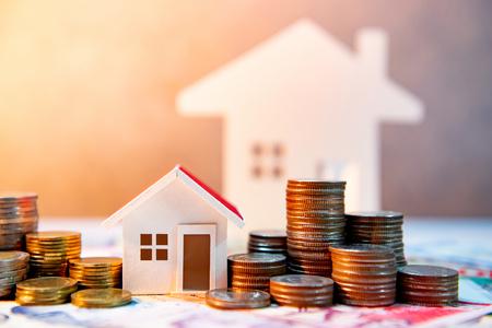 Inversión inmobiliaria o inmobiliaria. Tasa de préstamo hipotecario. Ahorrar dinero para el concepto de jubilación. Pila de monedas en billetes internacionales con modelo de casa en la mesa. Fondo de crecimiento empresarial