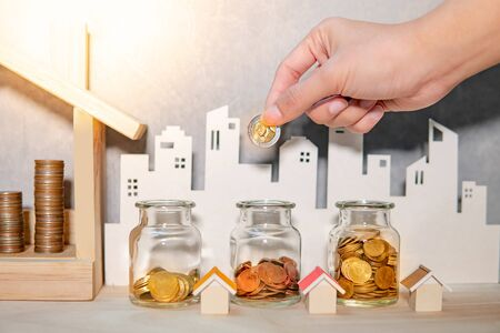 Saving money for real estate or property investment concept. Male hand holding gold coin and putting it in currency glass jar with coins stacked in house frame and city background on wooden table. Stock fotó
