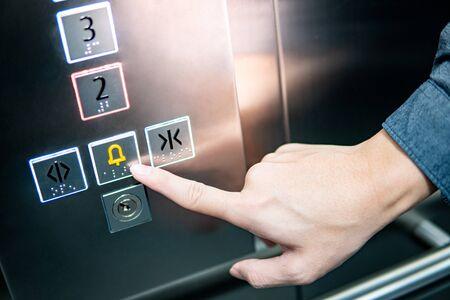 Dedo índice masculino presionando el botón de parada de emergencia y alarma en el ascensor (ascensor). Concepto de ingeniería mecánica
