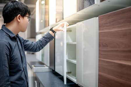 Asian man opening wooden cabinet door in furniture store choosing material to buy for house decoration. Home improvement concept