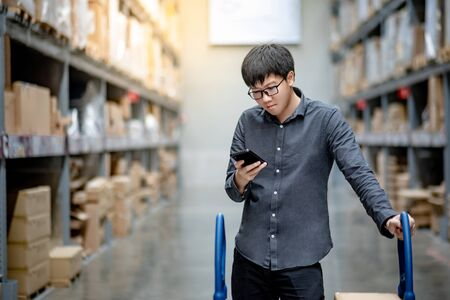 Asian guy shopper standing with shopping cart in warehouse inventory aisle checking shopping list on smartphone. Buying or purchasing factory goods. Shopaholic concept Stok Fotoğraf