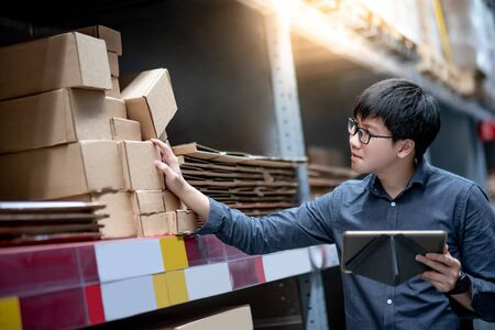 Young Asian man worker doing stocktaking of product in cardboard box on shelves in warehouse by using digital tablet. Physical inventory count concept Foto de archivo