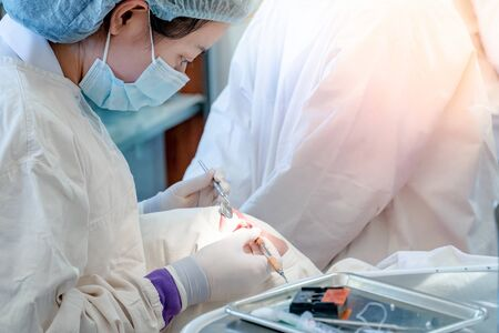 Female Asian dentist using instruments for examining and curing patient teeth in dental clinic. Dental procedure and medical treatment.