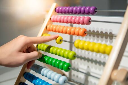 Male hand calculating with beads on wooden rainbow abacus for number calculation. Mathematics learning concept Stock fotó