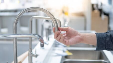 Male hand choosing stainless steel water tap in furniture store. Home improvement for domestic kitchen. Archivio Fotografico - 127828844