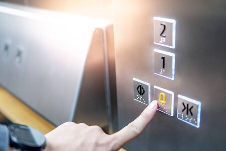 Male forefinger pressing on emergency stop and alarm button in elevator (lift). Mechanical engineering concept Stockfoto
