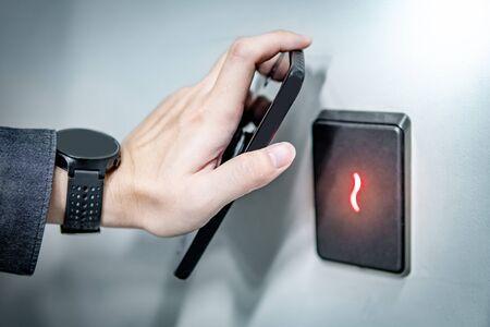 Mano masculina con smartphone para escaneo de sensores. Tecnología de sensor de infrarrojos para el acceso automático y la seguridad de la puerta. Foto de archivo