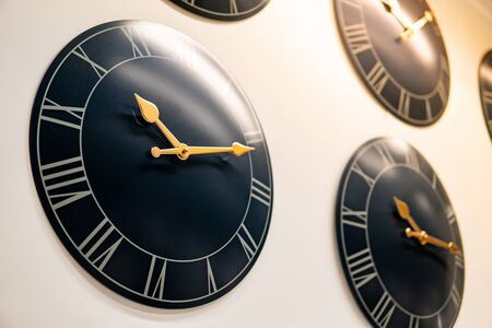 Group of antique round black wall clocks displayed on the wall in furniture store. Home decoration concept Stock Photo